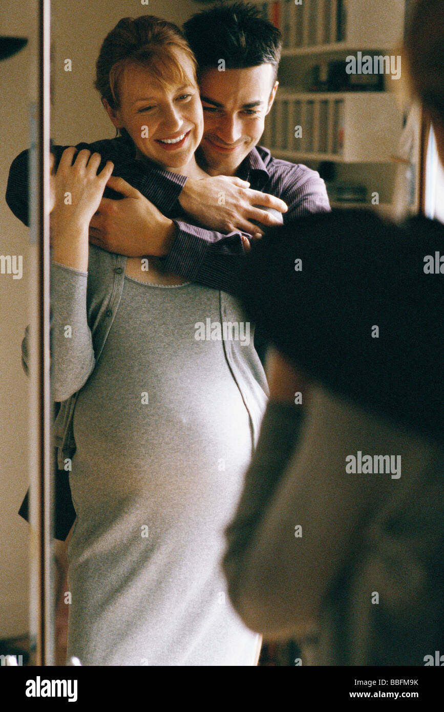Expecting couple embracing in front of mirror - Stock Image