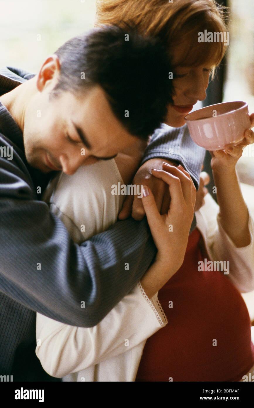 Man embracing pregnant wife, woman drinking tea - Stock Image