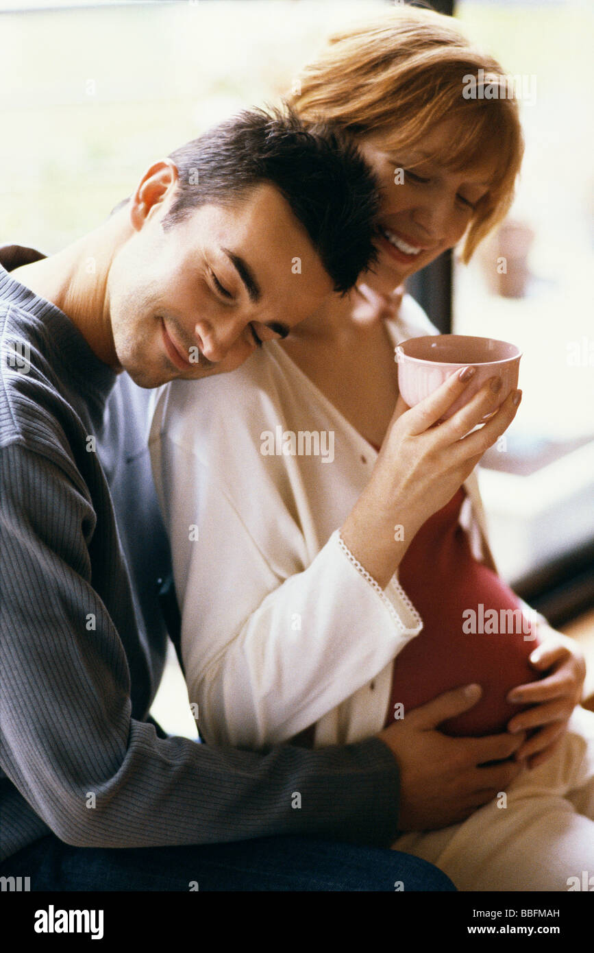 Man embracing pregnant wife, hands on her stomach, woman drinking tea - Stock Image