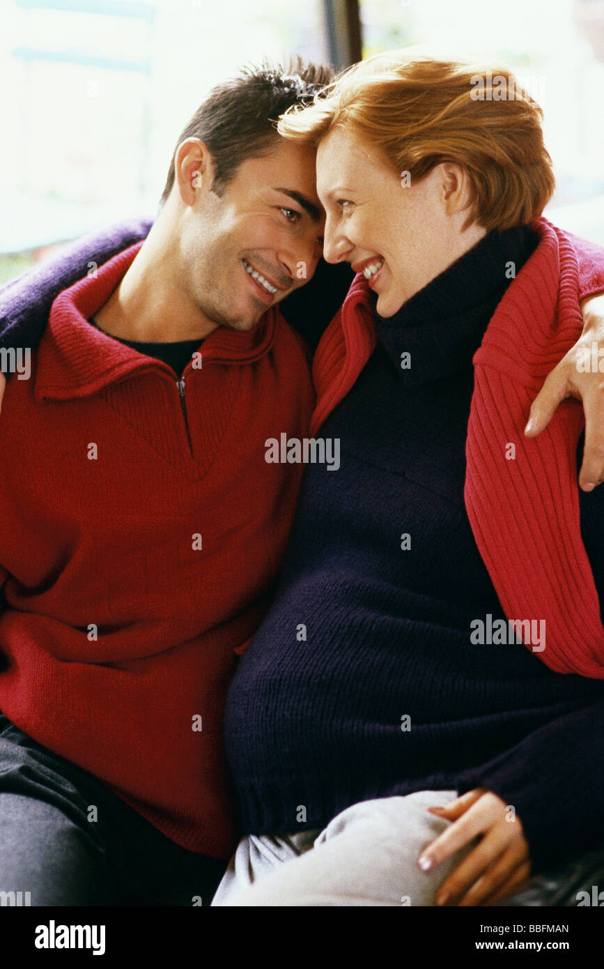 Expecting couple embracing, smiling - Stock Image