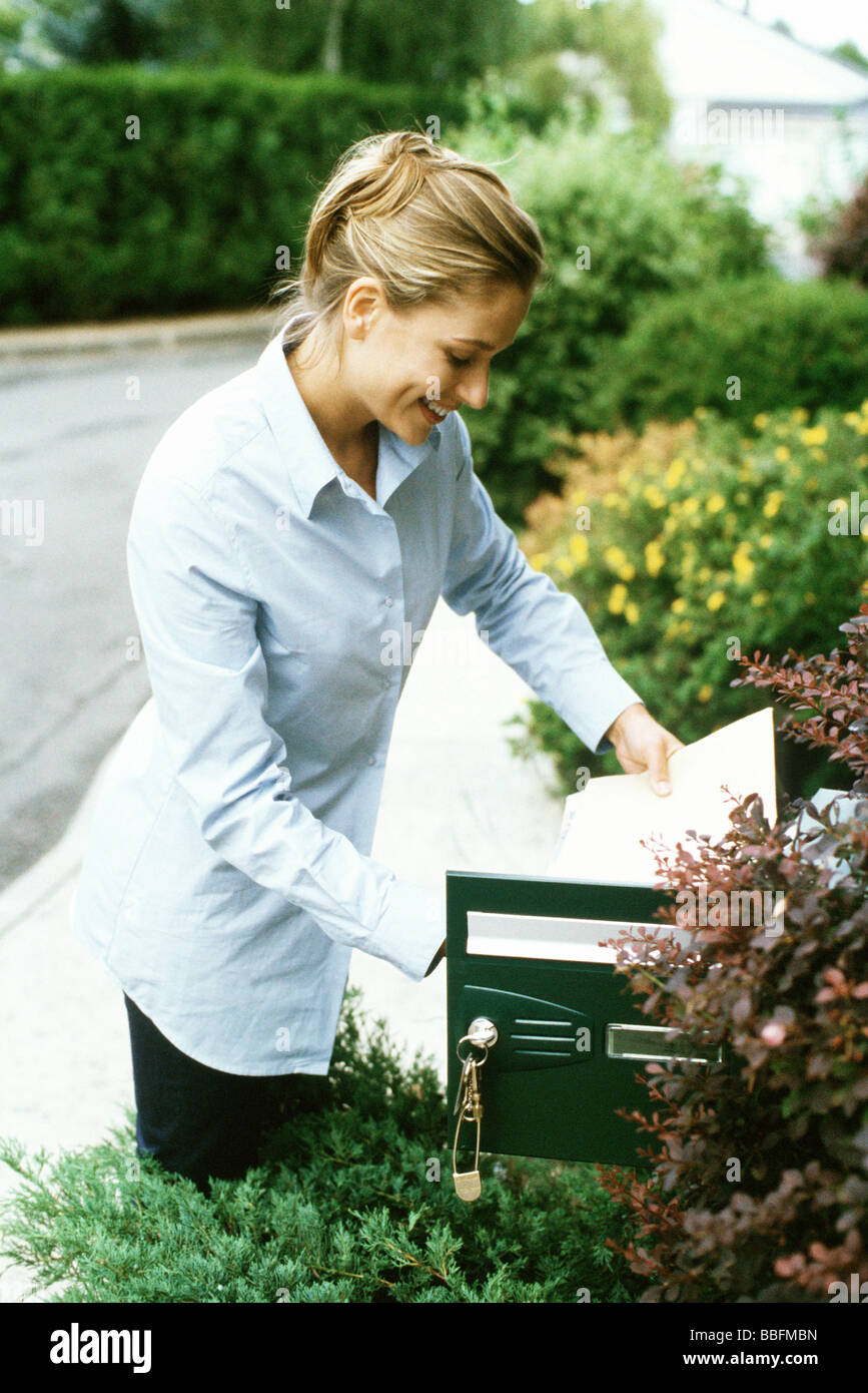 Woman checking mail, smiling - Stock Image