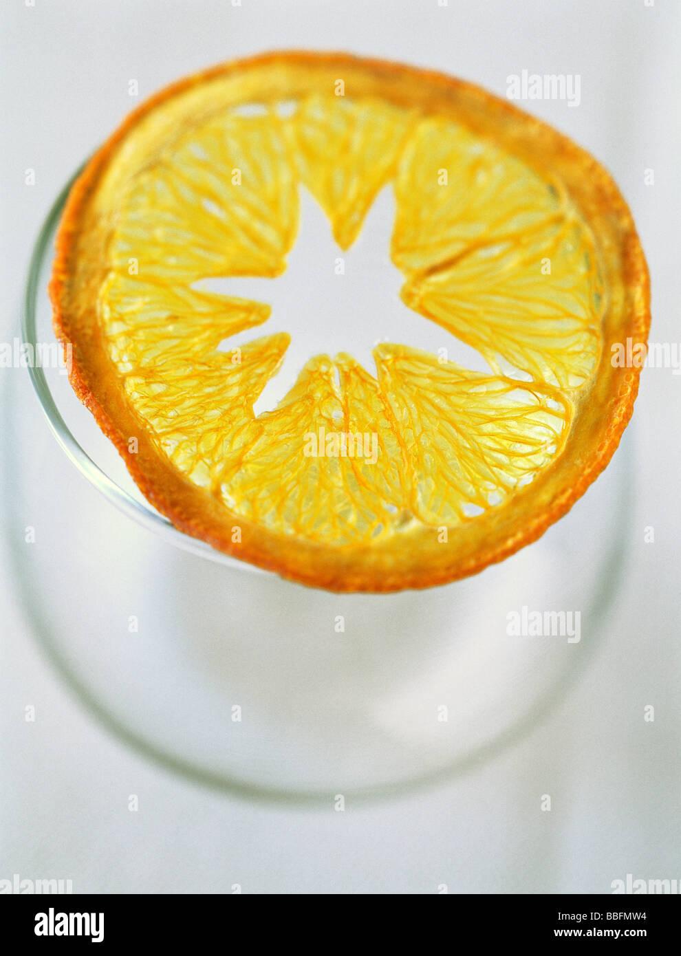Dried orange slice on top of glass - Stock Image