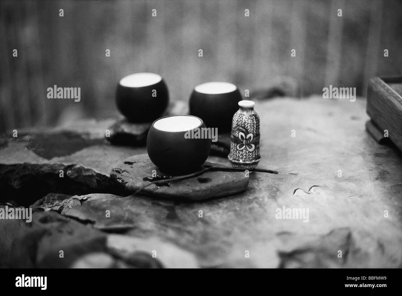 Tea cups placed on rock surface - Stock Image