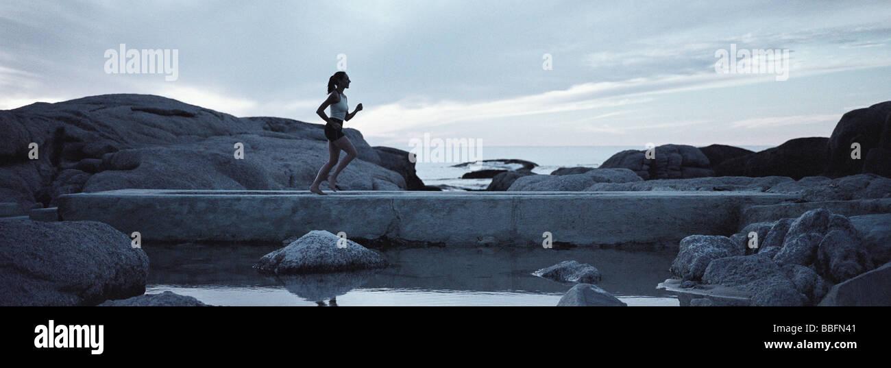 Woman running across footbridge near seashore in early morning - Stock Image