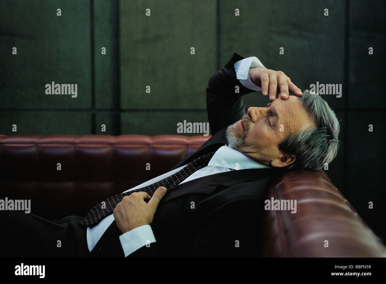 Businessman reclining on couch, hand on head, eyes closed - Stock Image