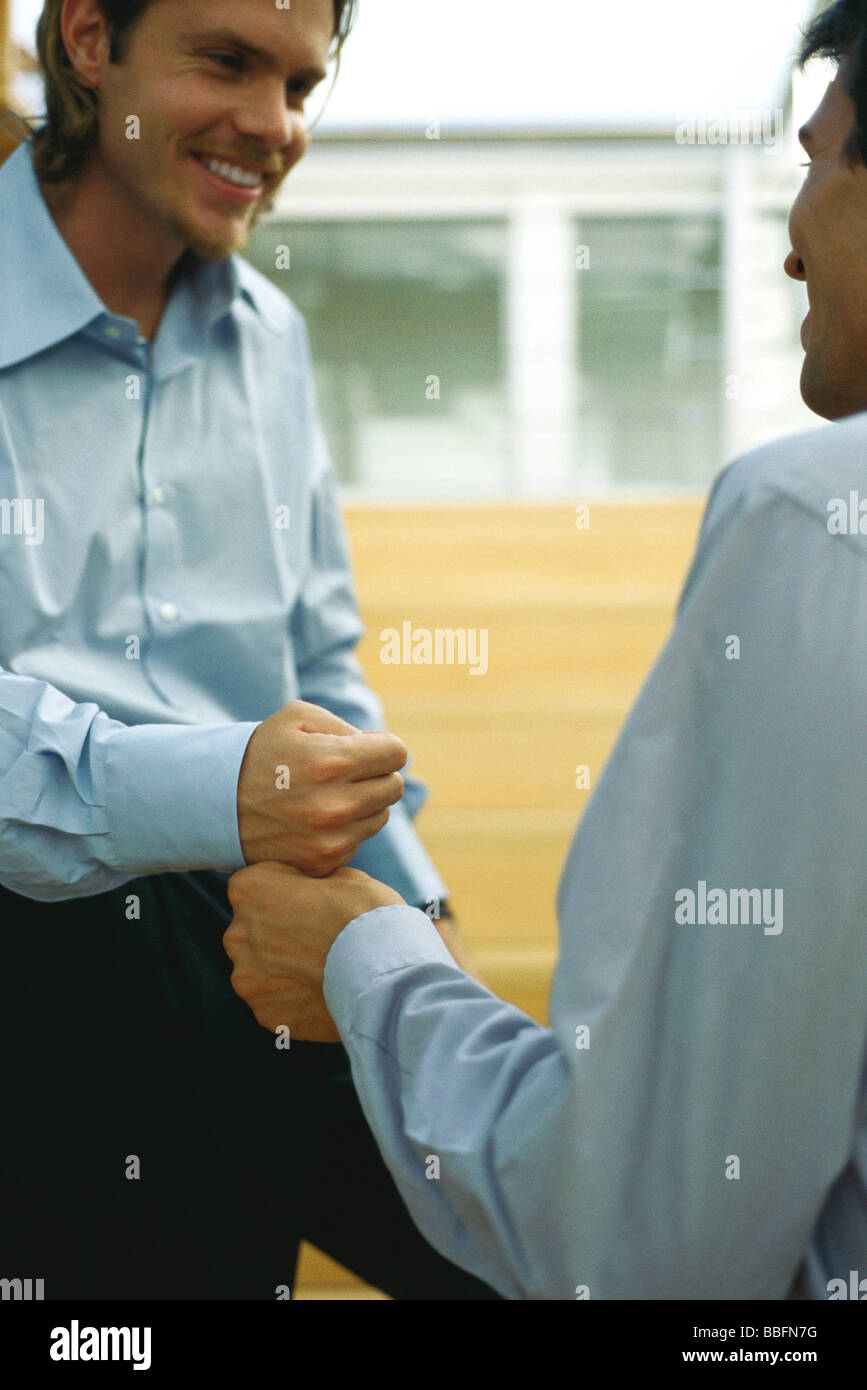 Two men touching fists - Stock Image