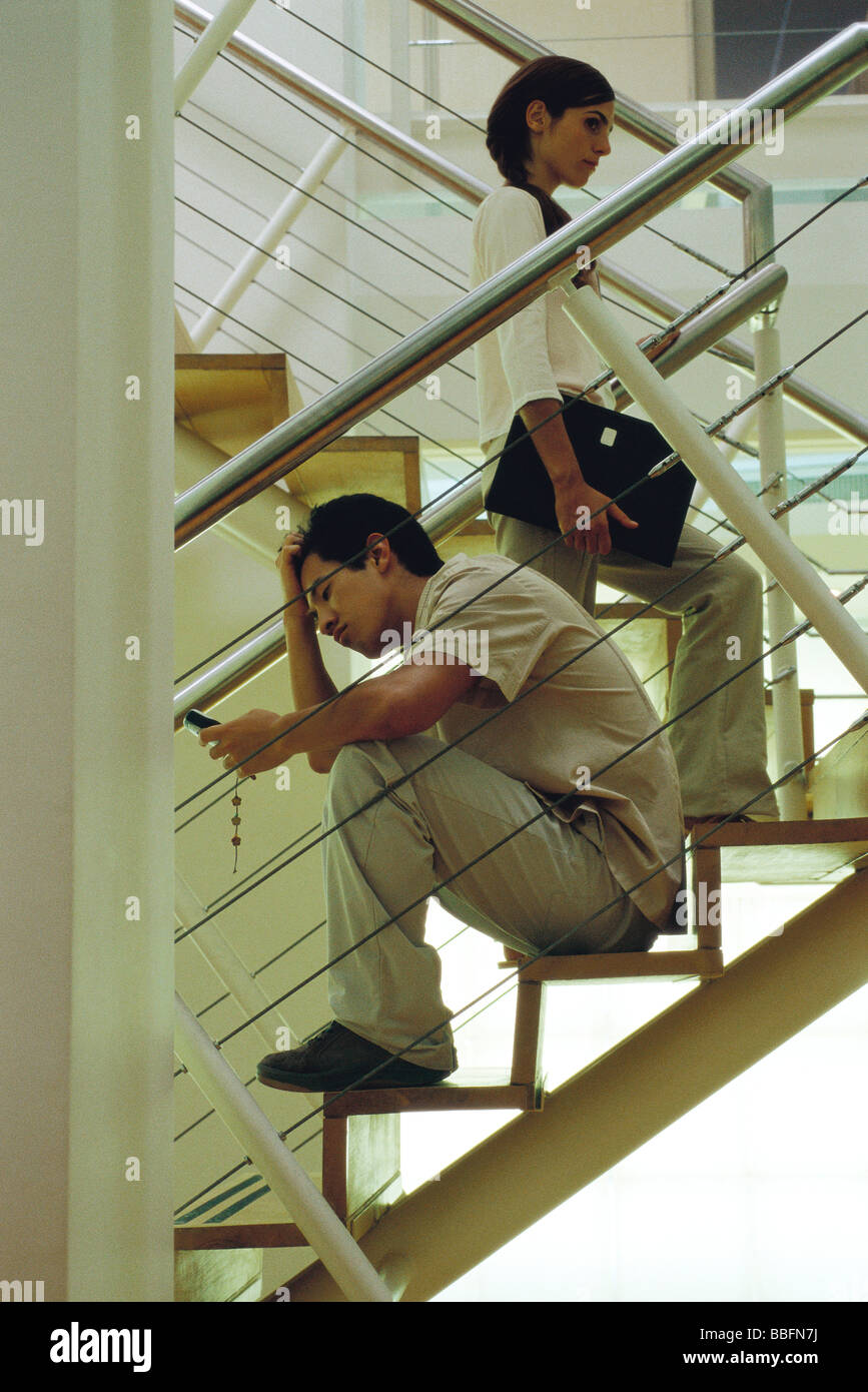 Man with hand on head sitting on stairs looking at cell phone, woman walking past Stock Photo