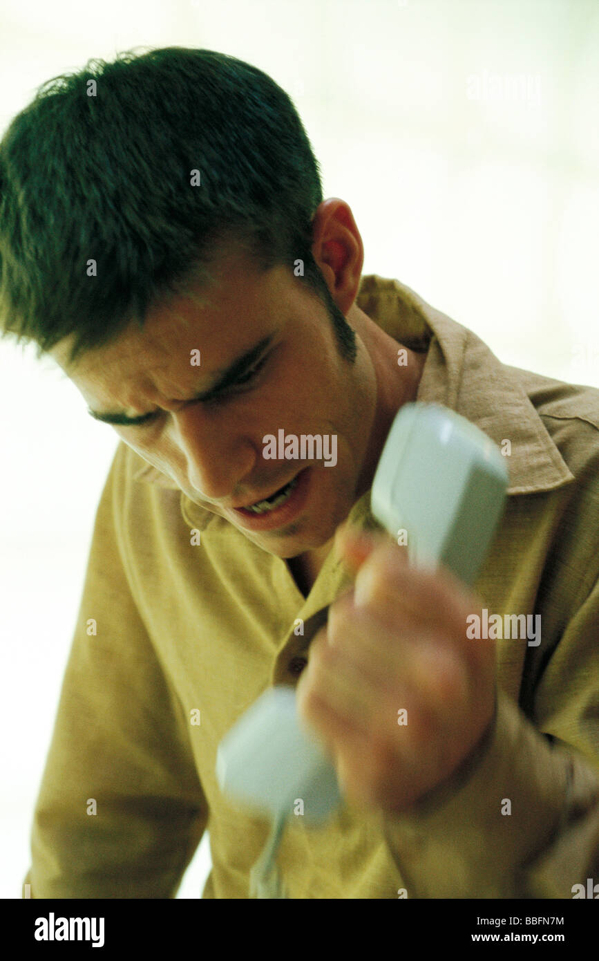 Man gripping phone receiver, furrowing brow - Stock Image