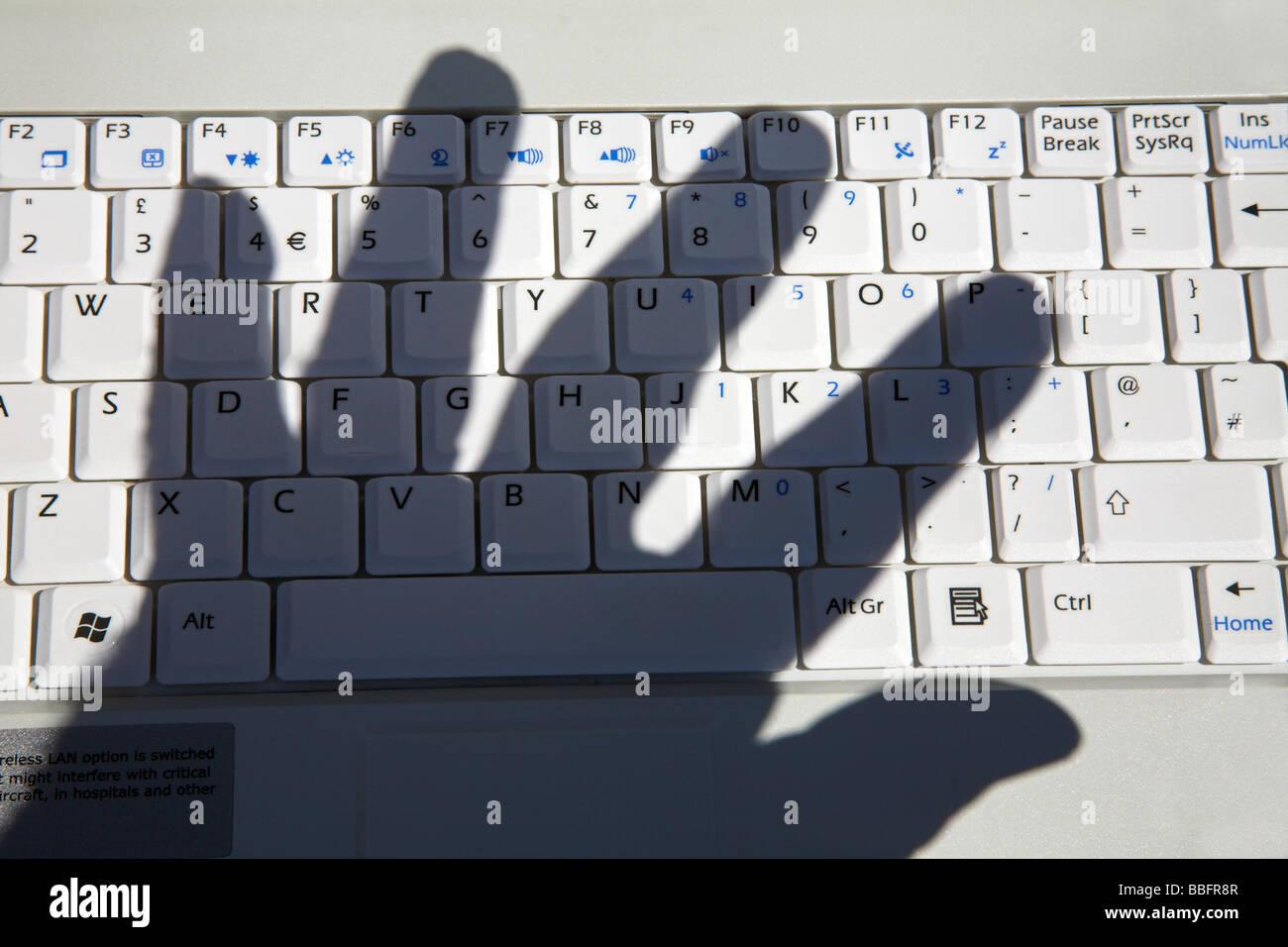 Shadow of hand over computer keyboard. - Stock Image