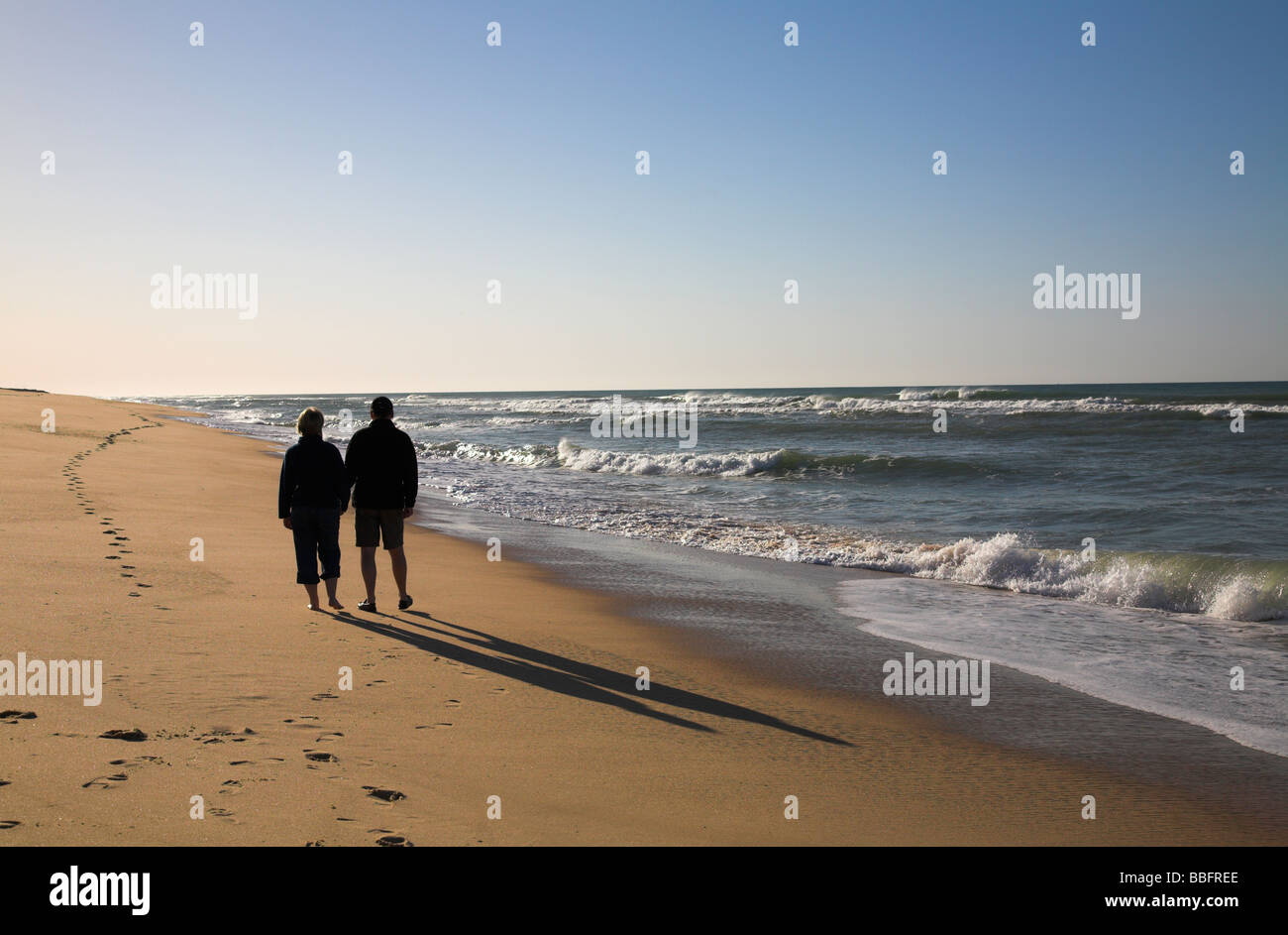 Couple strolling along the beach at sunrise.Stock Photo