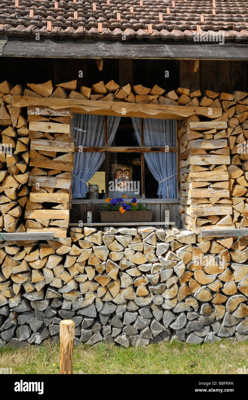 Firewood stacked around a barn with a manikin in the window, Mittenwald, Bavaria, Germany - Stock Image