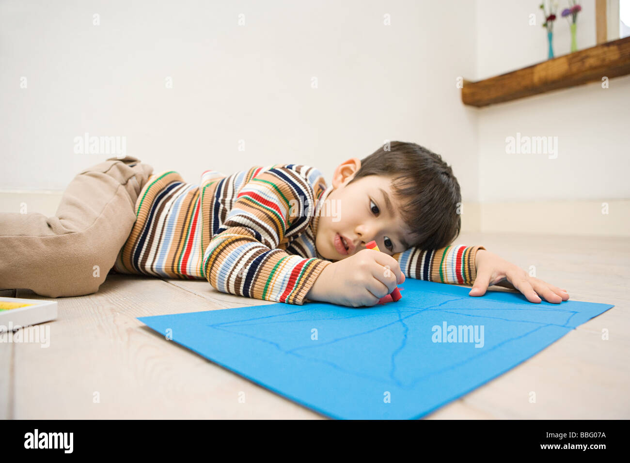 Boy holding a crayon - Stock Image