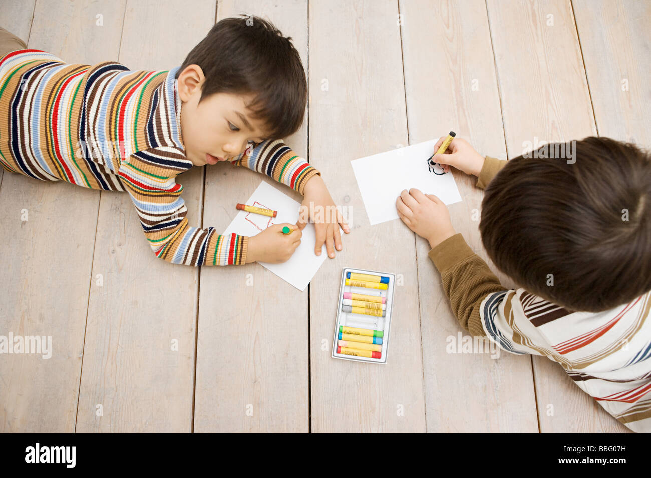 Boys drawing with crayons - Stock Image