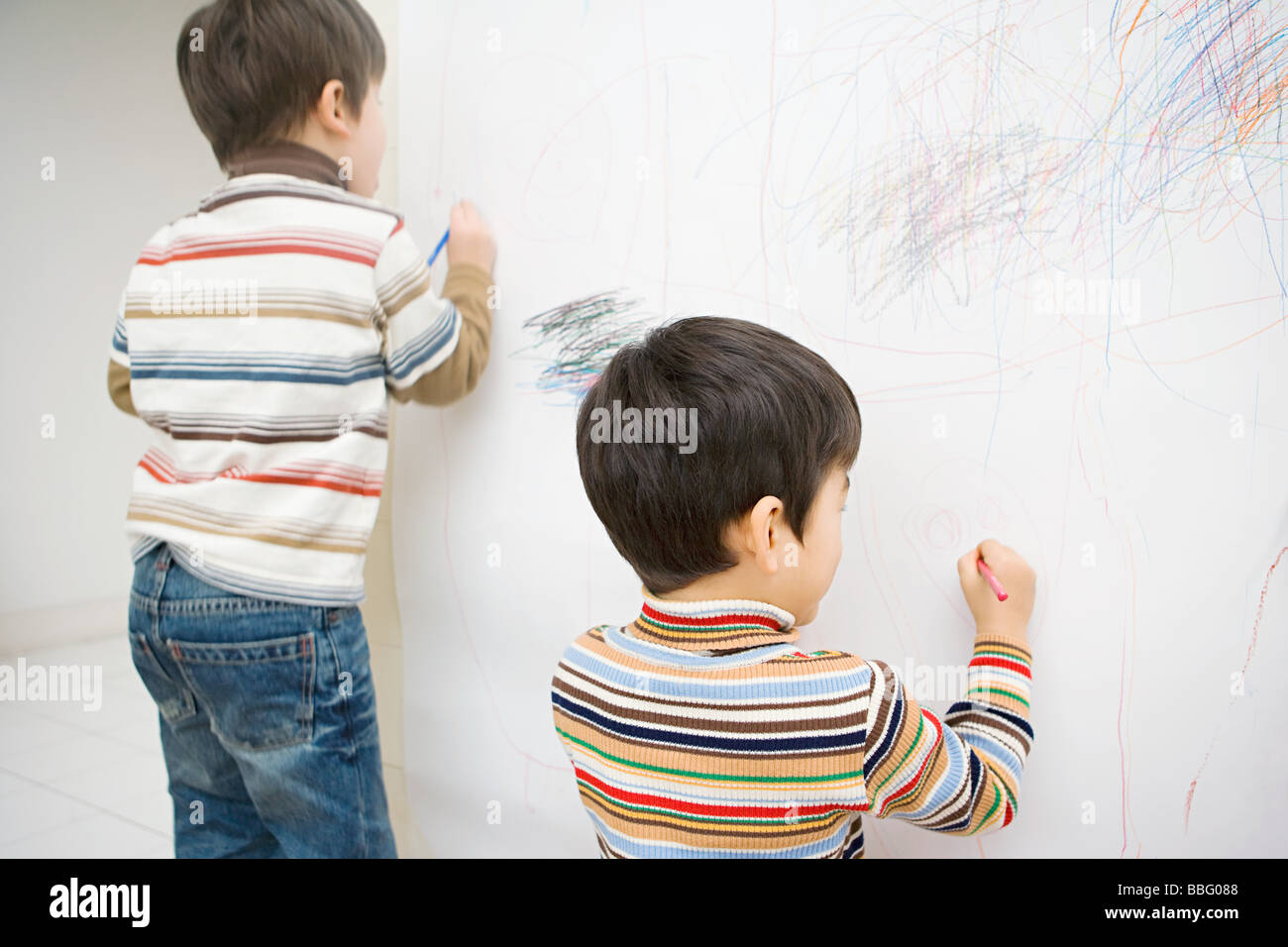 Boys drawing on a wall - Stock Image