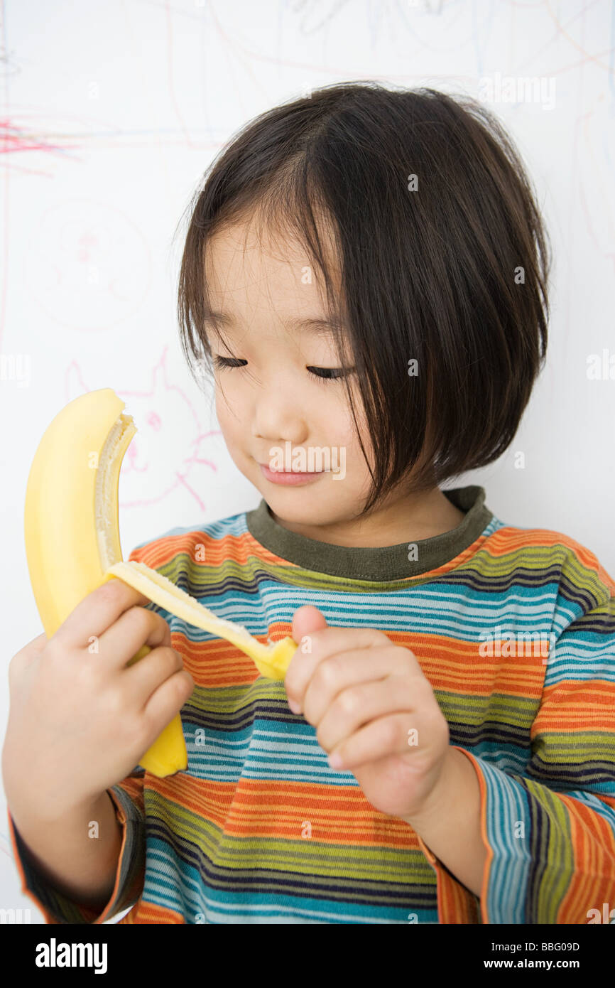 A boy peeling a banana - Stock Image