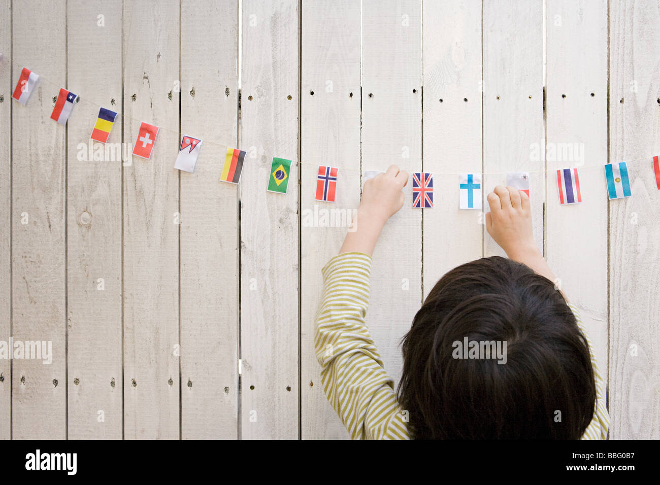 A boy reaching flags - Stock Image