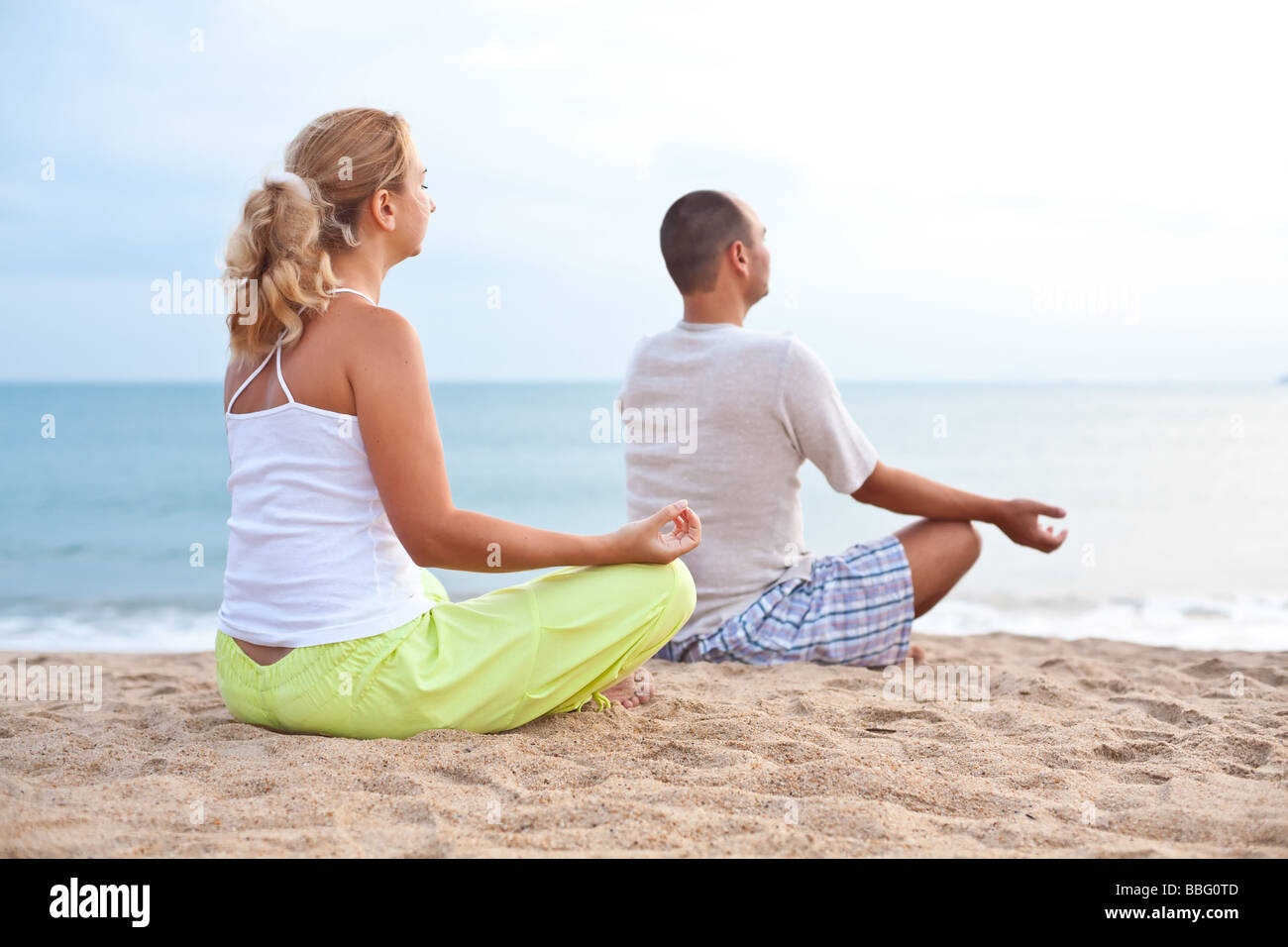 Young couple doing yoga exercises at sunrise time - Stock Image