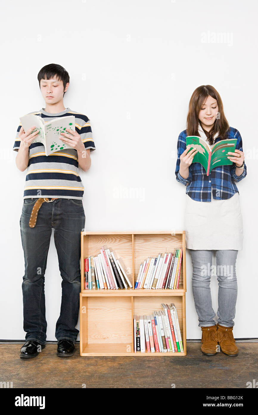 Young man and woman reading books - Stock Image