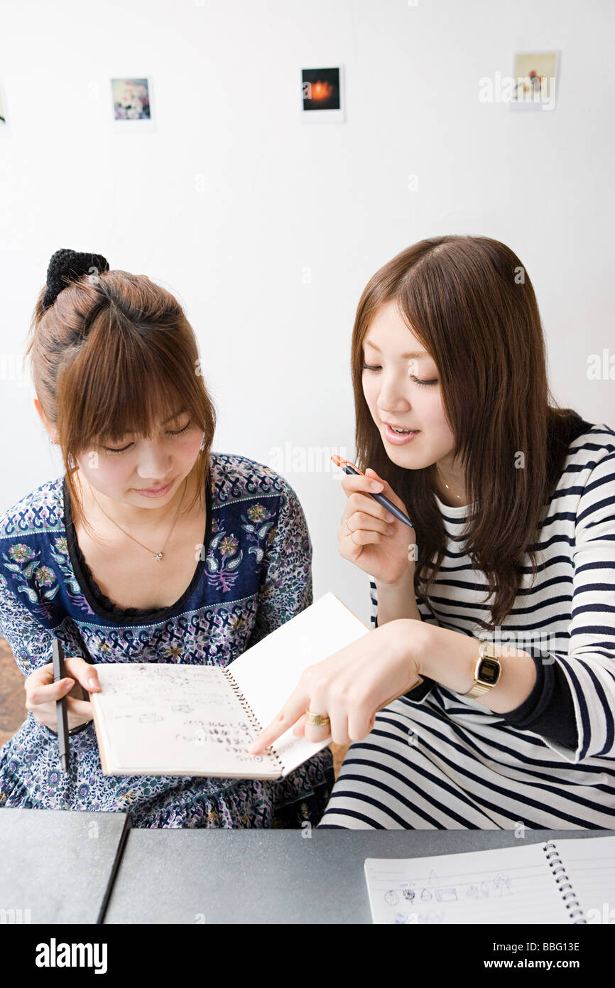 Young women looking at note book - Stock Image