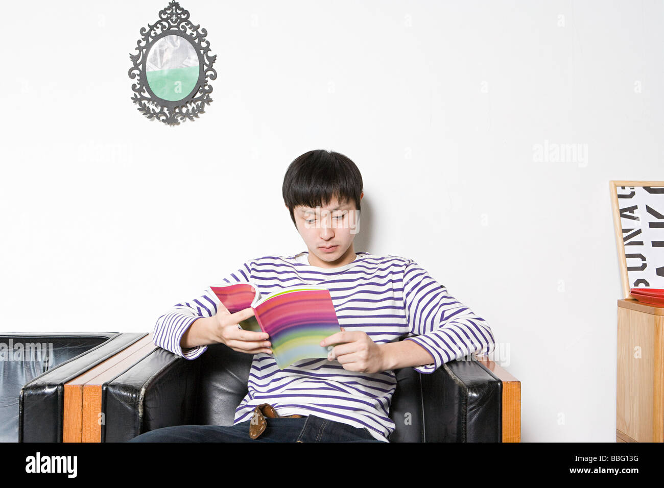 Young man looking at design book - Stock Image