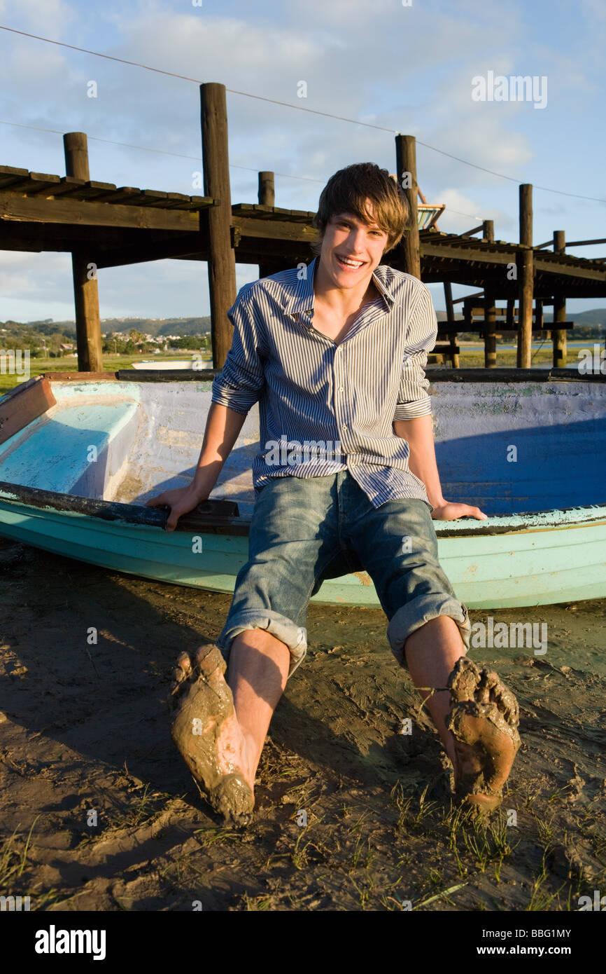 Teenage boy with rowboat - Stock Image