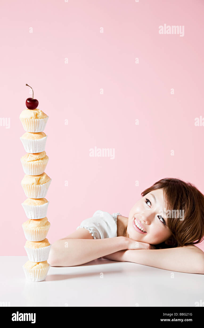 Woman looking at stack of cakes - Stock Image