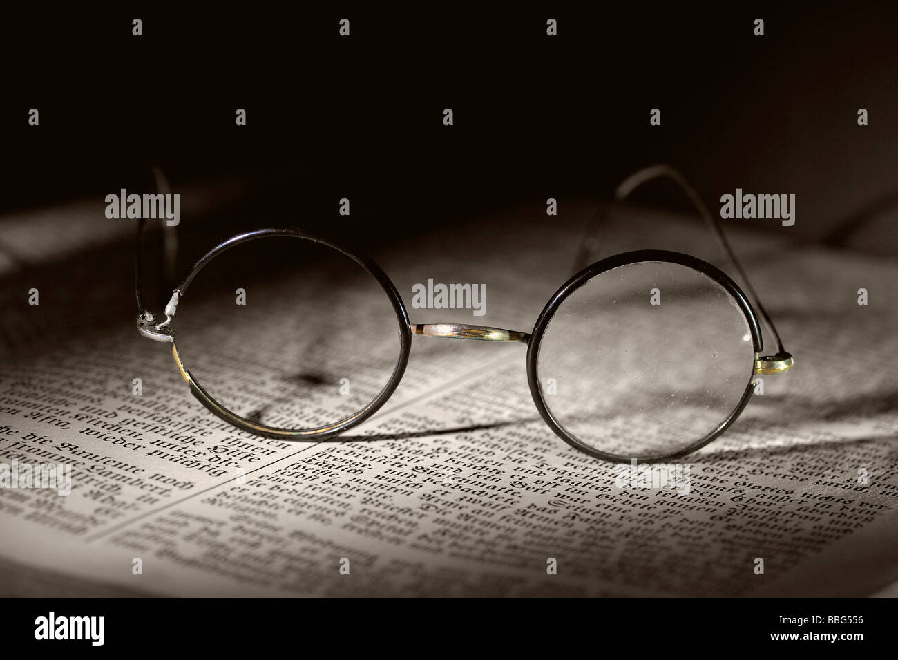 Old reading glasses on old book - Stock Image