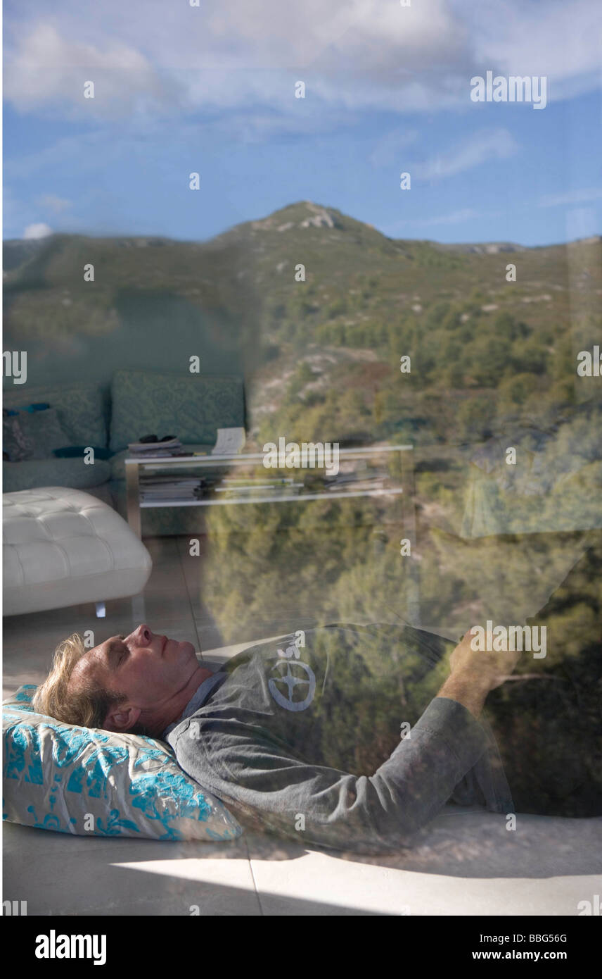Man sleeps on floor in living room - Stock Image