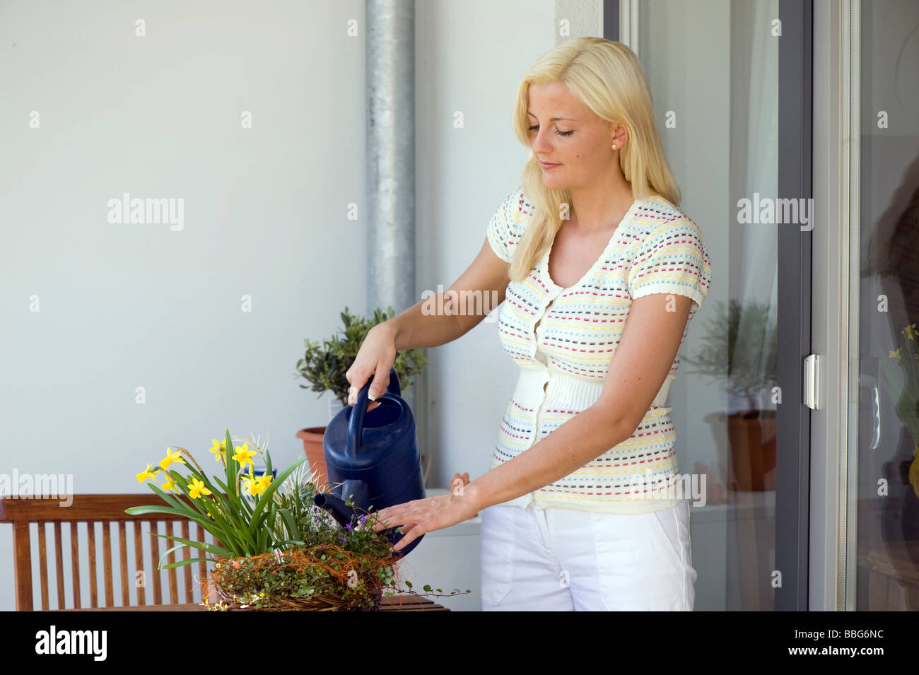 Young woman watering flowers on a balcony Stock Photo