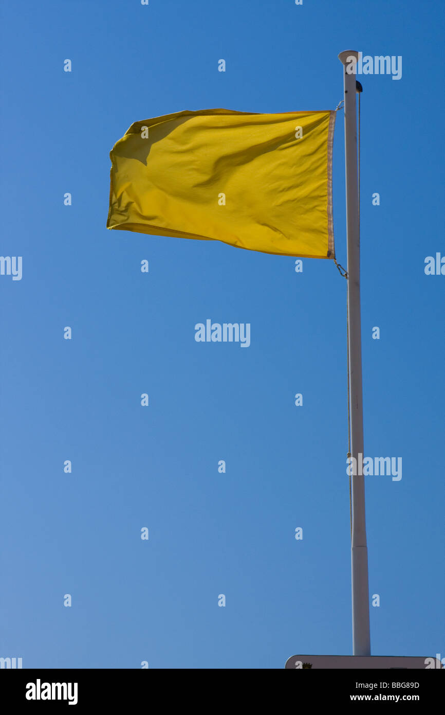 yellow flag waves against a bright blue cloudless sky - Stock Image
