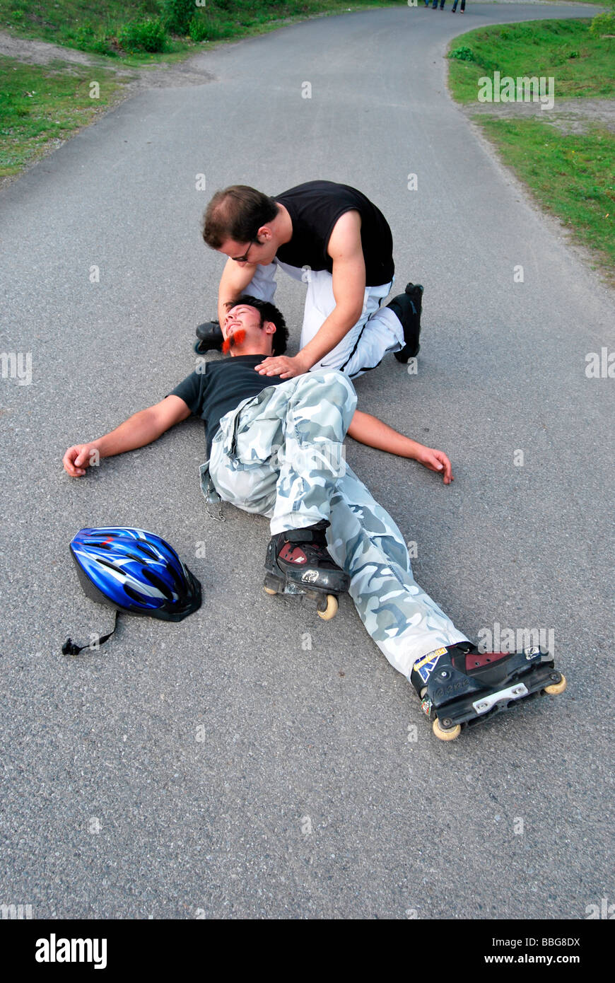 First aid, in-line skater on the floor after fall, motionless, person helping - Stock Image