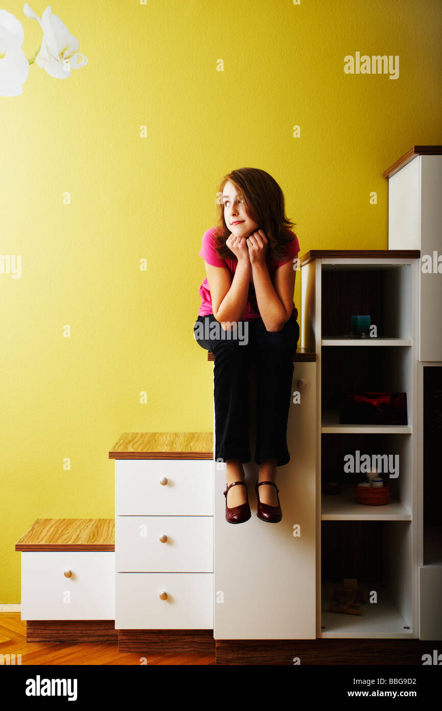 Young girl sitting on the steps of a chest of drawers - Stock Image