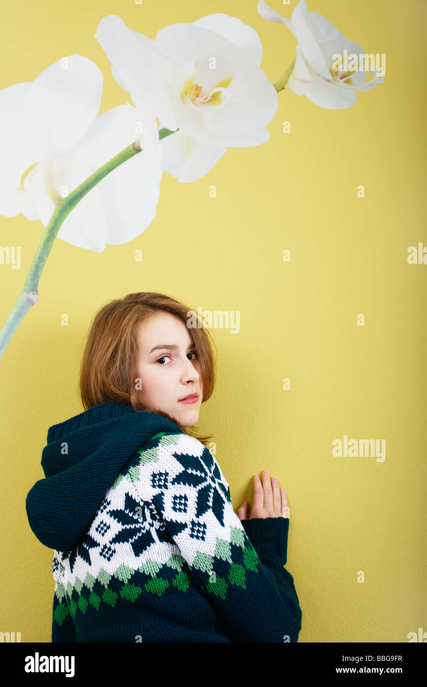 Young girl standing in front of a wallpaper with flower - Stock Image