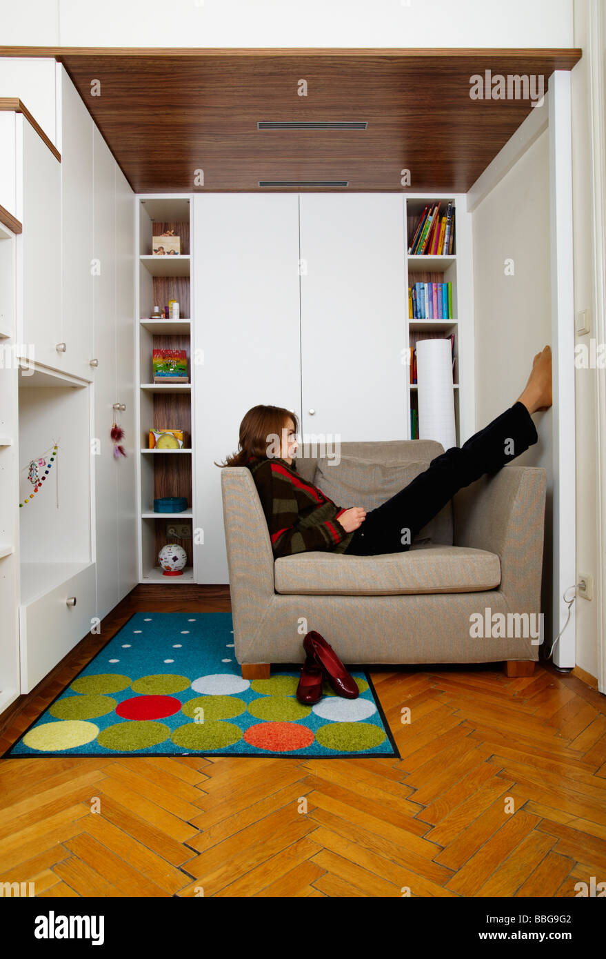 Young girl sitting on the armchair in her room Stock Photo