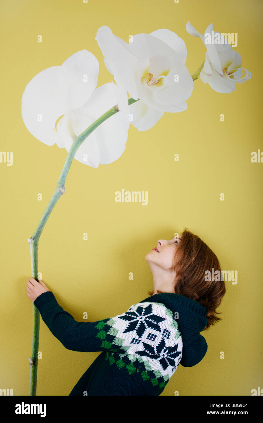 Young girl faces wallpaper with flower - Stock Image