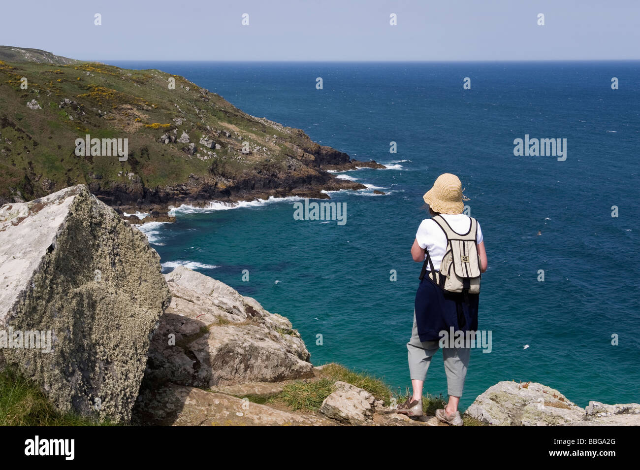 Female walker looking over Brea Cove to Carn Naun Point on the SWC footpath - Stock Image