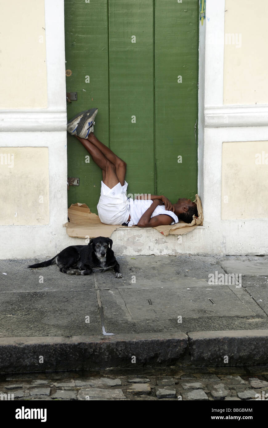 Homeless man sleeping in a house entrance guarded by his dog, Salvador, Bahia, Brazil, South America - Stock Image