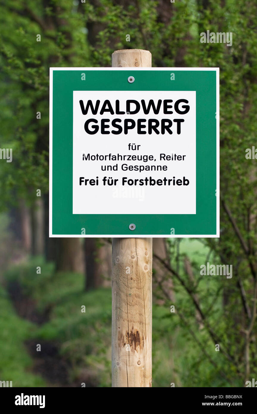 Sign: path is closed to vehicles, riders and teams, free for forest enterprise, trees in the back - Stock Image
