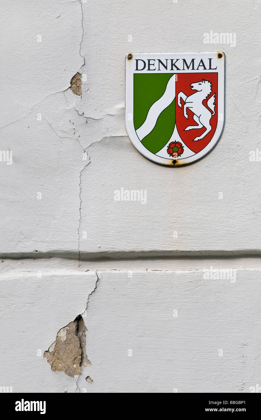 Sign of a protected monument at an old house wall in need of renovation, North Rhine-Westphalia - Stock Image