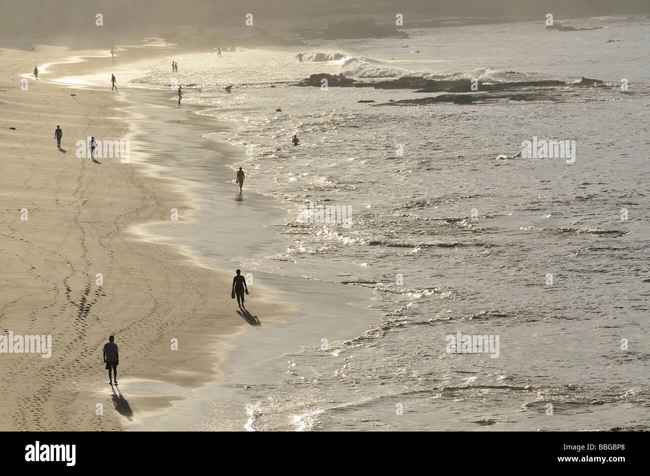 Walkers in the morning hour on the Praia do Farol da Barra beach, Salvador, Bahia, UNESCO World Heritage Site, Brazil, - Stock Image
