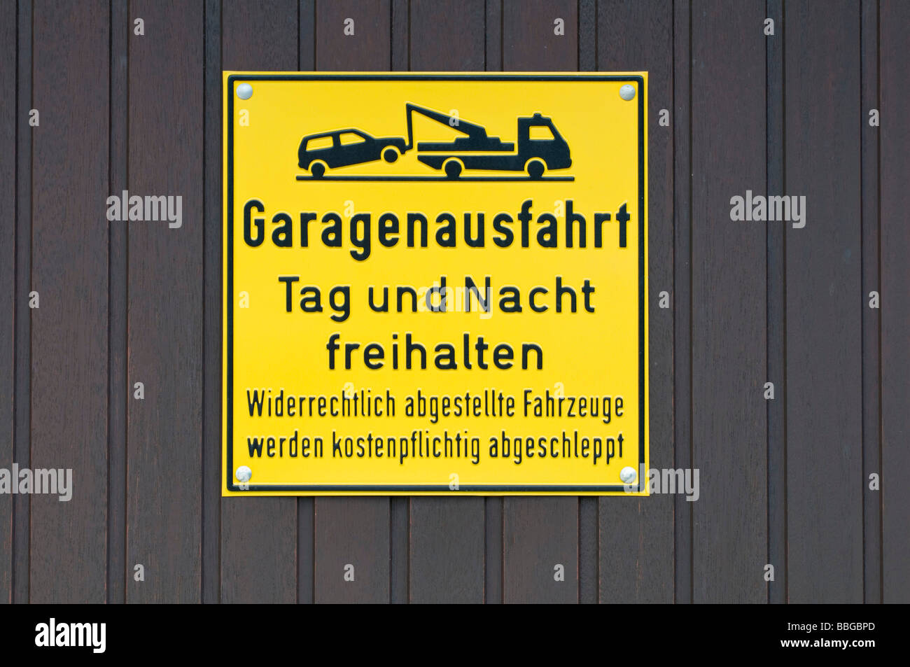Yellow sign on garage door, keep the garage exit accessible day and night, unlawfully parked vehicles will be towed - Stock Image