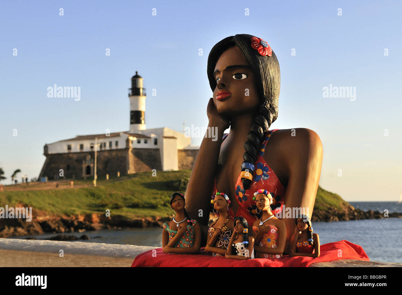 Traditional arts and crafts, clay figurine of a girl in love, namoradinha, and Forte de Santo Antonio da Barra fortress - Stock Image