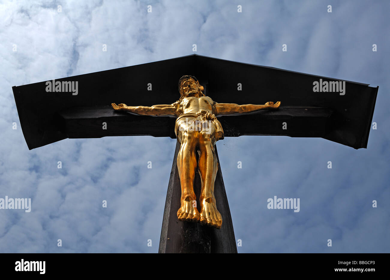Gold Jesus on the cross against an overcast sky, Kinding, Upper Bavaria, Germany, Europe Stock Photo