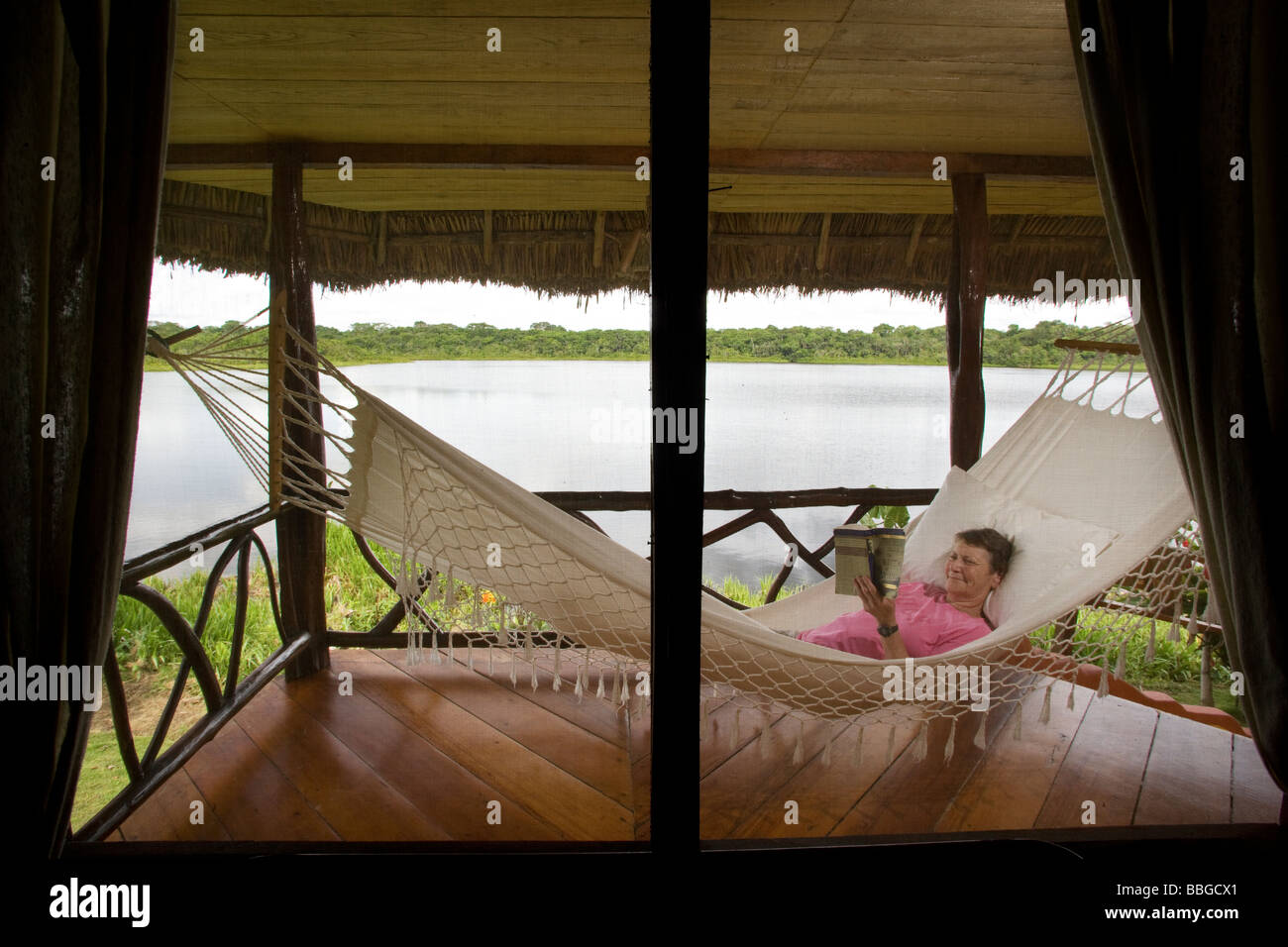Woman reading in hammock - Napo Wildlife Center - Yasuni National Park, Napo Province, Ecuador - Stock Image