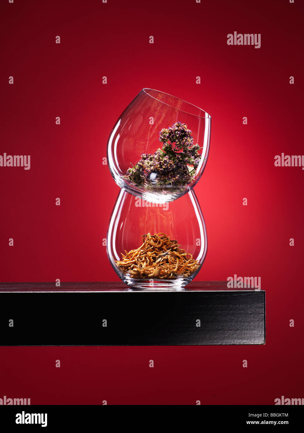 Spices in glass on walnut wooden shelf with deep red spotlit background - Stock Image