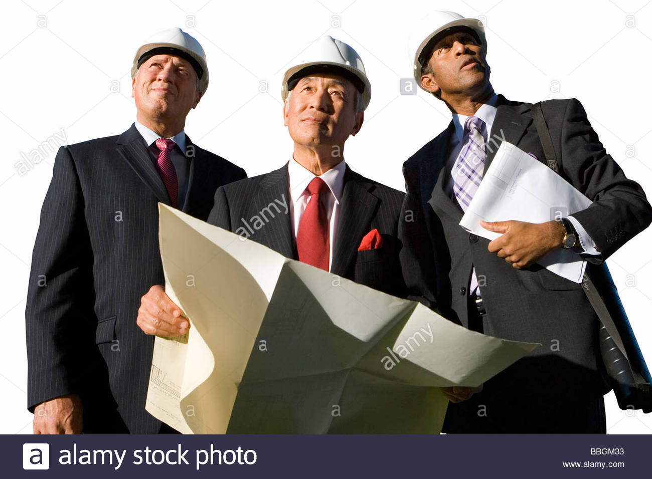 Businessman with blueprint by colleagues, in hardhats, low angle view, cut out - Stock Image