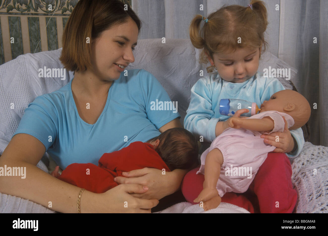 mother breastfeeding her baby while her toddler bottle feeds her doll - Stock Image