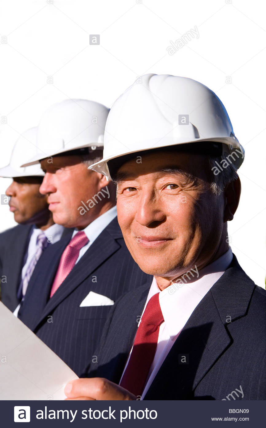 Businessman with blueprint by colleagues, in hardhats, cut out - Stock Image