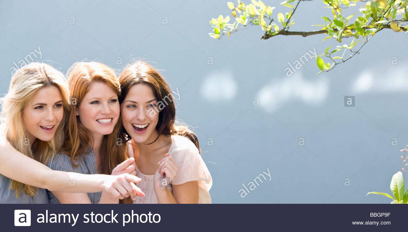 Three women looking at tree, Stuttgart, Baden-Wurttemberg, Germany - Stock Image