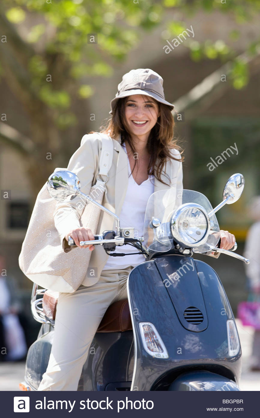 Young woman riding scooter outdoors, Stuttgart, Baden-Wurttemberg, Germany - Stock Image